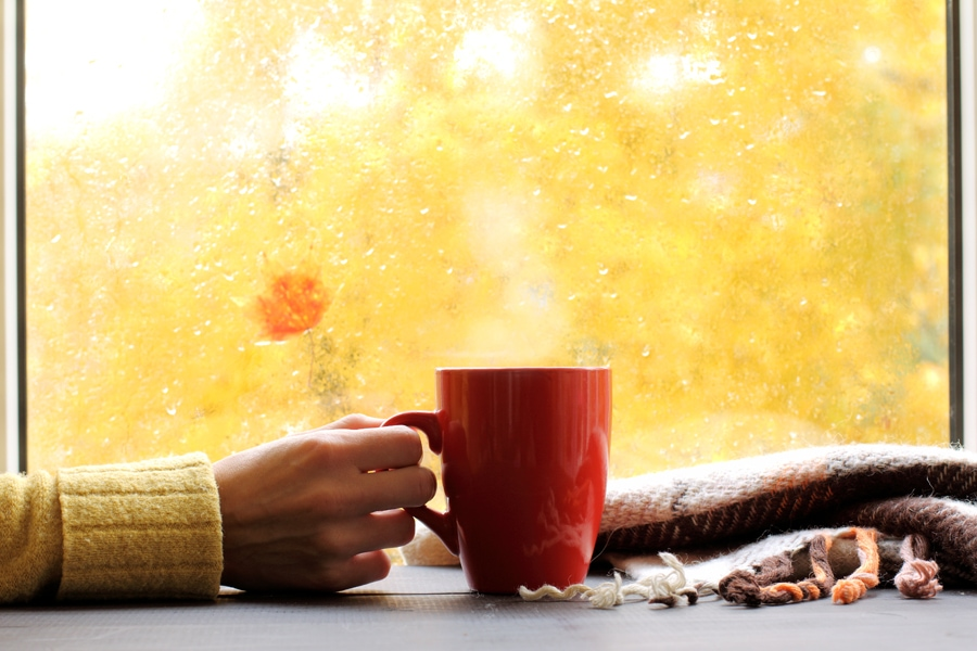 red mug of hot drink, when behind a window is rain in autumn in Salt Lake City